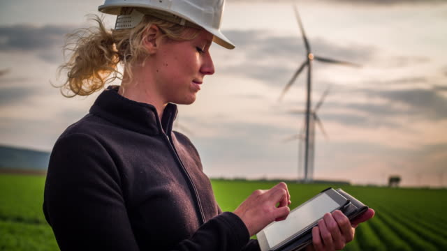 Female environmental engineer Women in front of wind turbines - Women in STEM