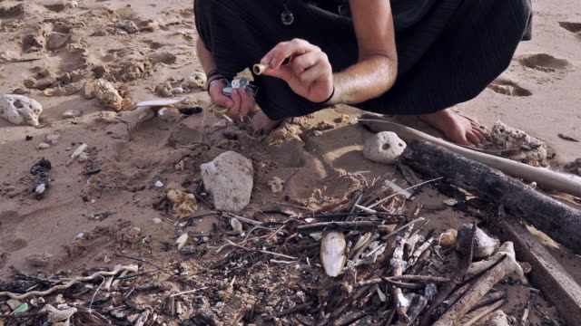 female environmentalist crouching on beach picking up microplastic pollution - tree hugging stock videos & royalty-free footage