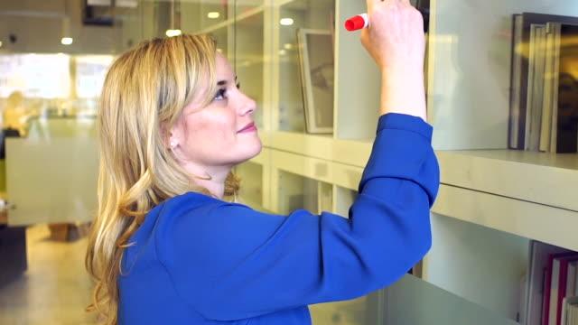 vidéos et rushes de female executive drawing on glass wall - une seule femme d'âge moyen