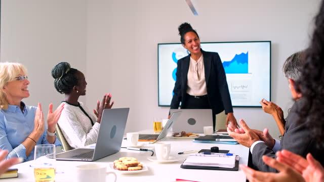 dirigente femminile che dà presentazione al team di gestione - strategia di vendita video stock e b–roll
