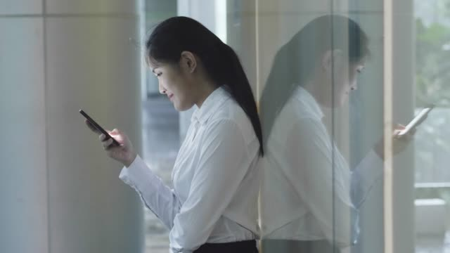 Female executive using phone against glass wall
