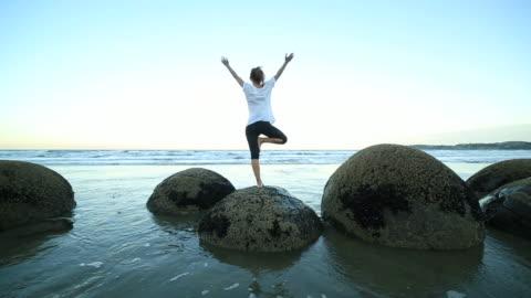 vídeos y material grabado en eventos de stock de mujer de ejercicios de yoga en boulder en el mar - vriksha asana