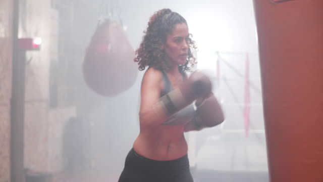 stockvideo's en b-roll-footage met female exercising with a a punch bag - stootzak fitnessapparatuur