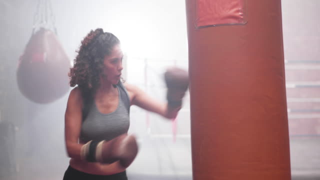 vidéos et rushes de female exercising with a a punch bag - musclé