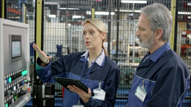 Female factory employee showing her male colleague the data entered into the touch screen on the machine's screen