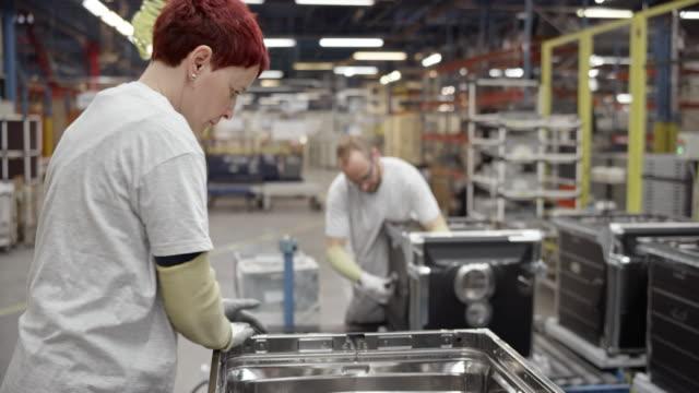 vidéos et rushes de ouvrier d'usine femelle vérifier le produit à son poste de travail - slovénie