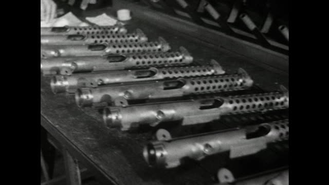 A female factory worker checks the the barrels of newly manufactured Sterling submachine guns with a measuring device