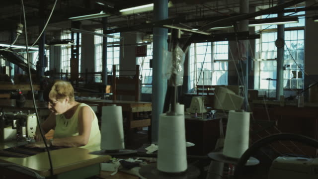 vidéos et rushes de female factory worker sewing at table - usine textile
