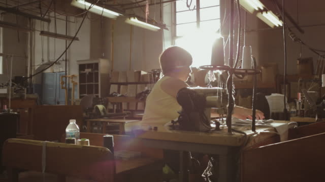 Female factory worker sewing at table