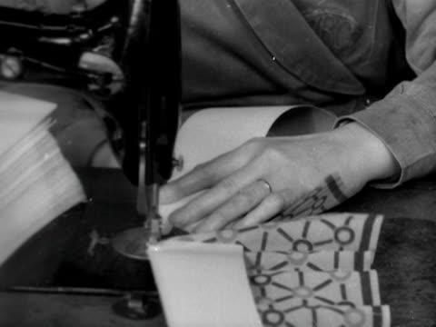 vídeos de stock e filmes b-roll de female factory worker sews a cardboard stiffener onto the back of paper party hats. 1950. - enfeites para a cabeça