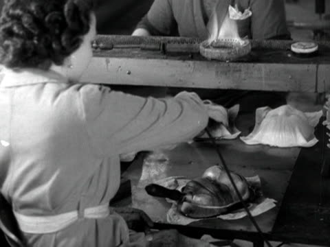 female factory worker uses a stencil and spray paint to finish off a monkey shaped party mask. 1950. - stencil stock videos & royalty-free footage