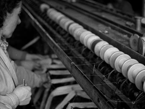 vidéos et rushes de female factory workers stand in front of bobbin machines which are weaving silk which will be used for the coronation robe for elizabeth the second... - tisser
