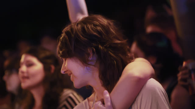 Female fans dance together in the front row of a rock concert