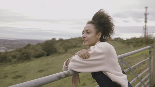female farmer leaning on gate looking out over farm land wearing dungarees, afro american female agriculture - mental health stock videos & royalty-free footage