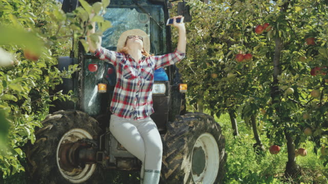 DS Female farmer punching the air while using a smart phone in the orchard