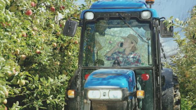 vidéos et rushes de fermier femelle ds parler sur un téléphone à l'intérieur d'un tracteur - tracteur