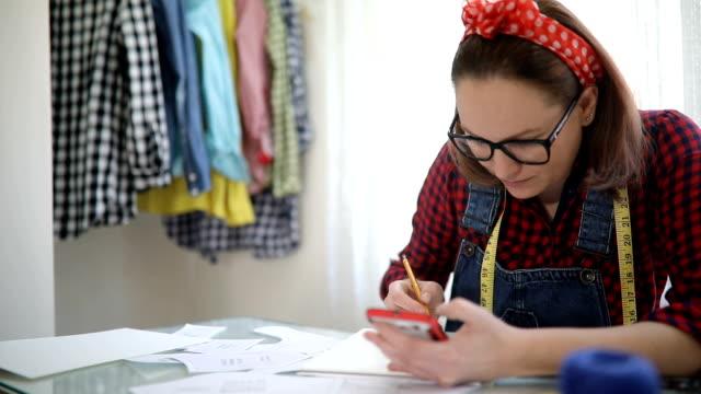 女性のファッション ・ デザイナーの手描画パッドと新しいドレスのスケッチを作るペンを保持しています。