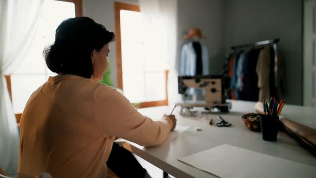 Weibliche Mode-Designerin im Atelier Schneider skizzieren