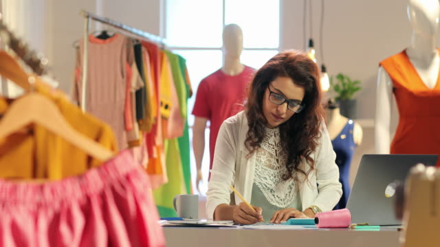 ms pan female fashion designer using laptop and preparing sketches on paper / delhi, india - fashion industry stock videos & royalty-free footage
