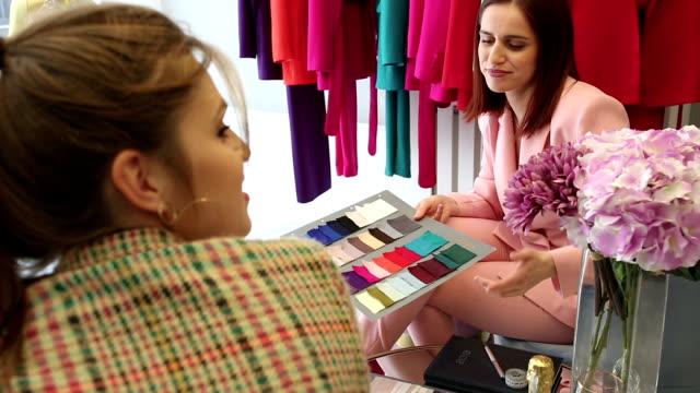 vídeos de stock, filmes e b-roll de desenhador de moda fêmea com auxílio no estúdio do projeto da forma - estilista de moda designer profissional