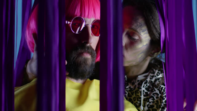 Female fashion model in stage make-up kisses male fashion model in pink wig and sunglasses, wearing yellow coat. Fashion video.