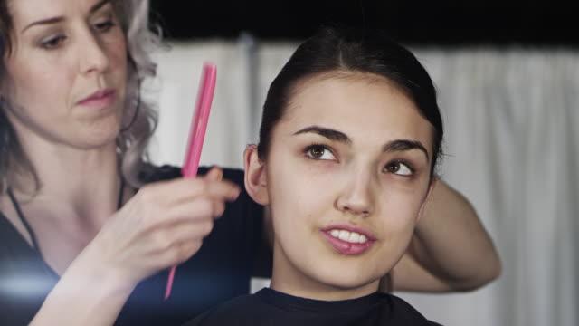 CU TD Female fashion model sitting in chair backstage at fashion show hairstylist styling models hair