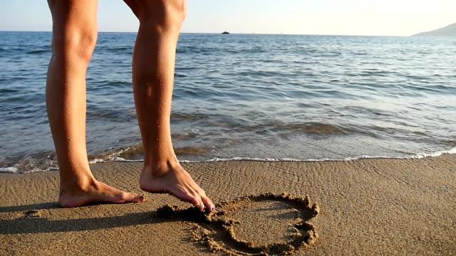 vídeos de stock e filmes b-roll de fêmea pés desenho corações na areia - parte do corpo humano