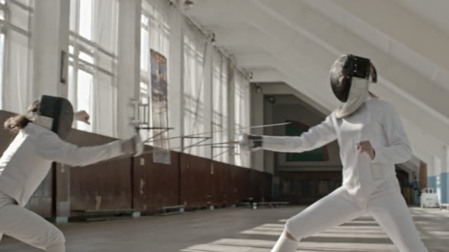 Female fencer getting hit during training