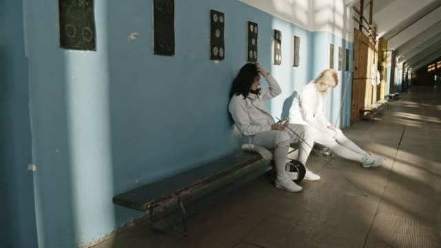 female fencers chatting on bench after workout - sports training stock videos & royalty-free footage