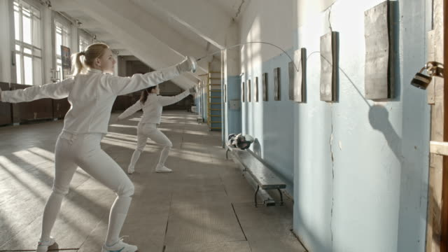 Female fencers doing exercise with foils