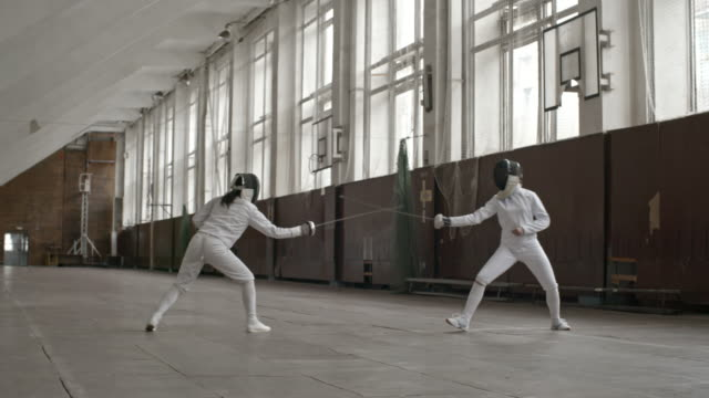 Female fencers parrying