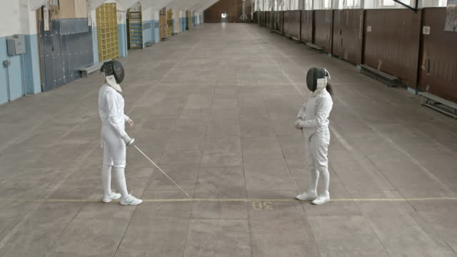 Female fencers practicing fight in gym