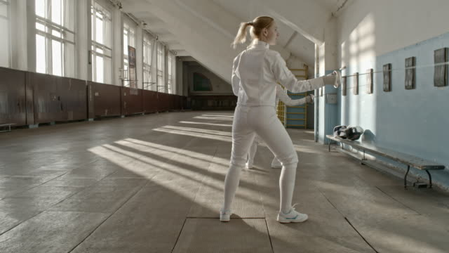 Female fencers practicing in gym