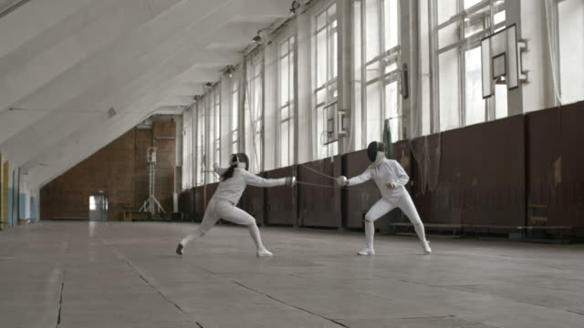 Female fencing athletes practicing in fight