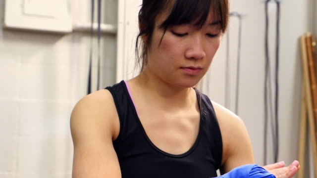 ms tu female fighter putting on hand wraps before workout in fighting gym - avvolto video stock e b–roll