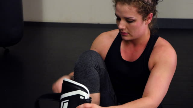 ms female fighter putting on shin guards before working out in fighting gym - 女子ボクシング点の映像素材/bロール