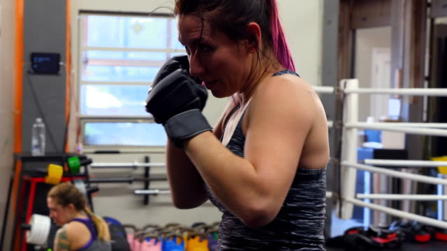 ms pan female fighter using punching mitts to train in gym - 女子ボクシング点の映像素材/bロール