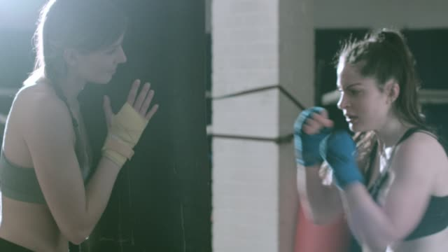 Female fighter working with trainer in gym