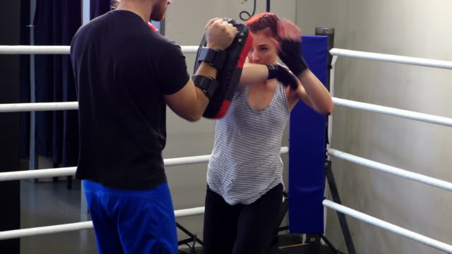 ms pan ts female fighter working with trainer in ring in gym - aggressione video stock e b–roll