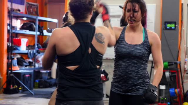 MS Female fighters grappling and working out together in fighting gym