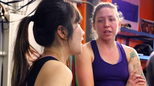 ms female fighters in discussion during training session in gym - 女子ボクシング点の映像素材/bロール
