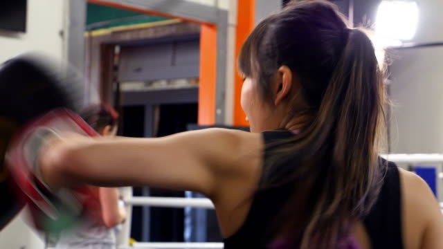 MS PAN Female fighters using punching mitts to train in gym