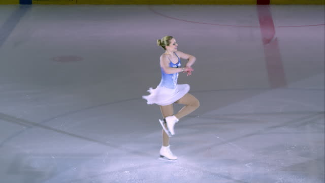 SLO MO Female figure skater ending performance with a spin