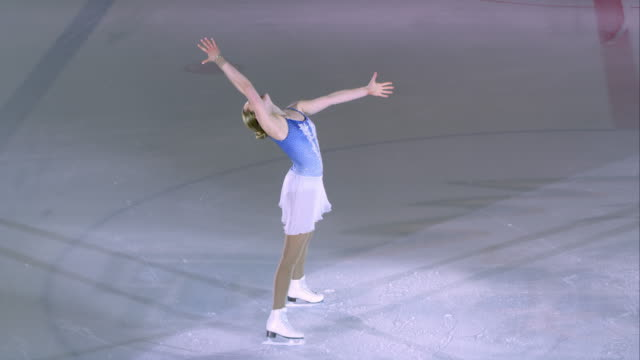 slo mo female figure skater energetically ending her performance - figure skating stock videos and b-roll footage