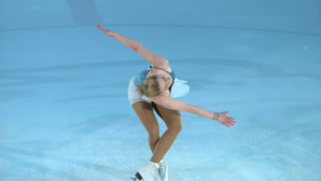 slo mo ld female figure skater in a centered sit spin variation - figure skating stock videos & royalty-free footage