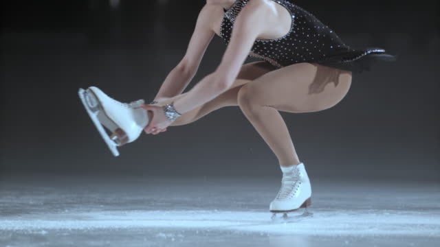 SLO MO Female figure skater in a sit spin variation