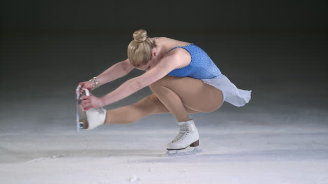 SLO MO LD Female figure skater in a sit spin