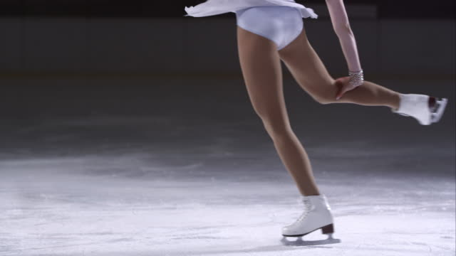 SLO MO TU Female figure skater in an upright spin variation