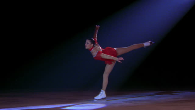 female figure skater in red costume skating, turning + posing gracefully in spotlight - figure skating stock videos & royalty-free footage