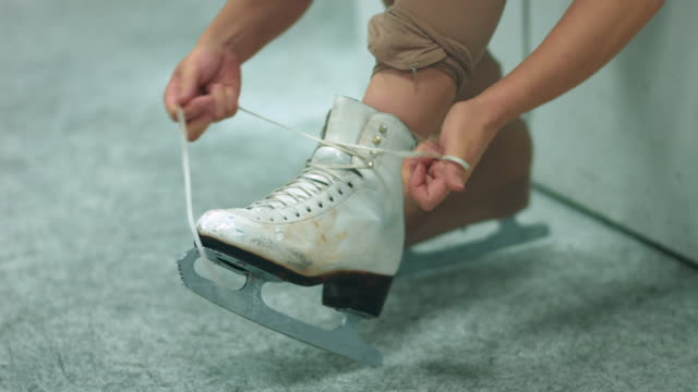 a female figure skater lacing up skates - アイススケート点の映像素材/bロール